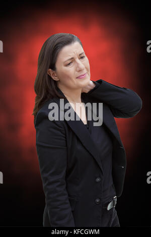 Middle aged woman with chronic pain syndrome fibromyalgia suffering from acute neckache, on red and black background - Stock Image