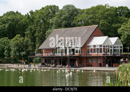 Llandrindod Wells lake swans and ducks and lakeside restaurant building, Powys Wales UK. - Stock Image