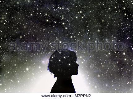 Silhouette of woman's head in galaxy of stars - Stock Image