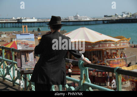 Brighton, UK - September 1 2018: A street artist works on his oil canvas of the Brighton Palace Pier and funfairs along the beachfront on 1​ September 2018.   The Pier, in the central waterfront section, opened in 1899 houses amusement rides as well as food kiosks.Credit: David Mbiyu /Alamy Live News - Stock Image