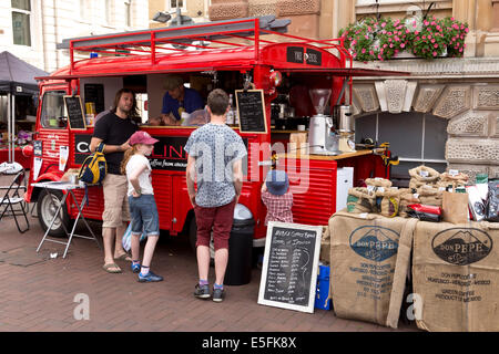 Family buying drinks from a coffee van in Ipswich market square. - Stock Image