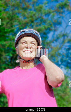 Senior woman in front of bushes and blue sky in summer sun with pink sport shirt, cycling gloves and helmet talking - Stock Image