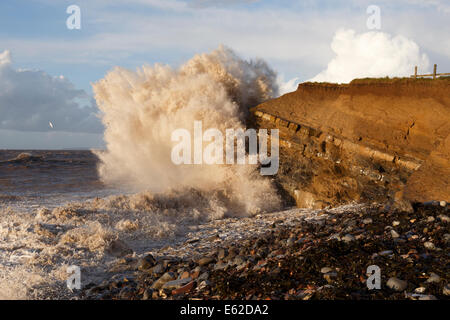 High tide at Kilve, with waves crashing against cliff.   Colour of wave clearly demonstrating how the rock face - Stock Image
