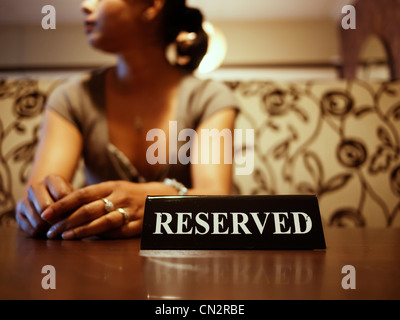 Punjabi woman waits at reserved table - Stock Image