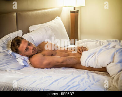 Shirtless sexy male model lying alone on his bed - Stock Image