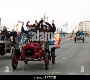 Mr Rick Lindner and his passengers celebrating, after they completed the 2018 London to Brighton Veteran Car Run, in  a 1904 Ford. - Stock Image