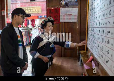 Lijiang. 22nd Apr, 2019. A local resident introduces hieroglyphics to a tourist in the Lijiang ancient town in southwest China's Yunnan Province, April 22, 2019. According to local authority, tourism started to heat up when a faster train service was launched between Lijiang and provincial capital Kunming in early 2019. During the first season, Lijiang welcomed 12.325 million arrivals and saw a total revenue of 25.637 billion yuan, up 21.5 percent and 15.13 percent respectively than the previous year. Credit: Hu Chao/Xinhua/Alamy Live News - Stock Image