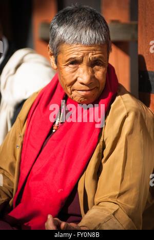 Elderly Buddhist nun sitting in sun on terrace at Paro Dzong, Bhutan - Stock Image