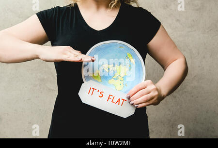 Flat Earther concept. Person who believes that Earth is flat disc. Anonymous woman holding flat Earth model in front of body with text: It`s flat. Iso - Stock Image