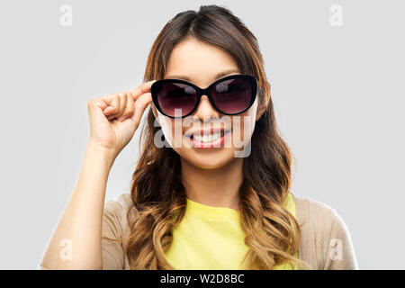 happy smiling young asian woman in sunglasses - Stock Image
