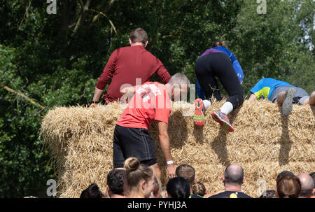 Obstacle course runners climbing a straw bale wall - Stock Image