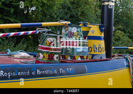 Buckby watering cans decorated in Roses and Castles canal art, Stoke Bruerne, UK - Stock Image