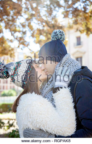 Young couple dressed in winter clothes and wool hats kiss passionately in a public park - Stock Image