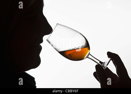 Worker smelling whisky in distillery - Stock Image