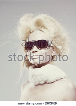 Young woman wearing sunglasses and fur scarf - Stock Image