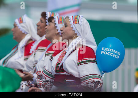 RUSSIA, Nikolskoe village, Republic of Tatarstan 25-05-2019: A group of mature women dancing traditional dance. A balloon with a name of Political Par - Stock Image