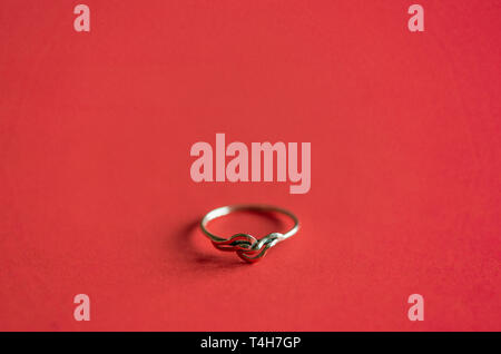 Close up / macro of a gold ring on coral red coloured background - Stock Image