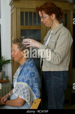 Two European over 40 friends dying hair at home - Stock Image