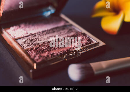 palette with crushed powder eyeshadows in nude and blush tones on dark background, concept of beauty and make-up trends - Stock Image