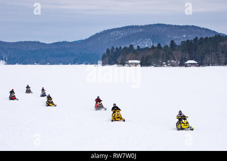 A group of 7 snowmobiles racing across Lake Pleasant in the Adirondack Mountains, NY USA - Stock Image