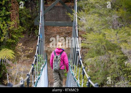 Female hiker viewed from behind crossing a swing bridge in the Abel Tasman National Park, New Zealand - Stock Image