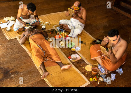 Horizontal aerial view of Kathakali performers putting on their distinctive make up in Kerala, India. - Stock Image