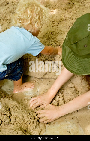 Two young children playing in sand and water - Stock Image