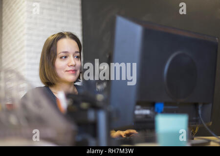 Businesswoman working at computer in office - Stock Image