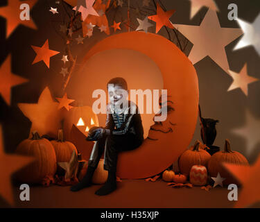 A boy is wearing a halloween skeleton costume on an orange moon prop with night stars in a studio for a magic or - Stock Image