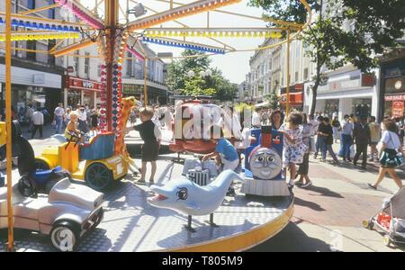 Children's carousel, Queens Street, Cardiff, Wales. Cymru. Circa 1980's - Stock Image