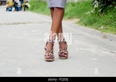 Crossed legs of a young woman on high shoes posing in the street. - Stock Image