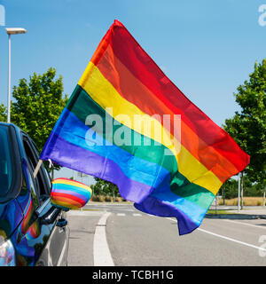 closeup of a rainbow flag in the wing mirror of a car in the street and another rainbow flag popping up from the window - Stock Image