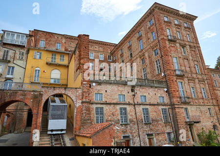 MONDOVI, ITALY - AUGUST 18, 2016: Funicular train and ancient bricks buildings in a sunny summer day in Mondovi, Italy. - Stock Image
