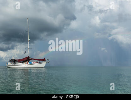 Sailboat floating in the Atlantic Ocean with a rainbow behind it - Stock Image