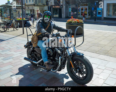 Rider in town centre pulling away on a 1200 cc Harley Davidson FORTY EIGHT motor cycle - Stock Image