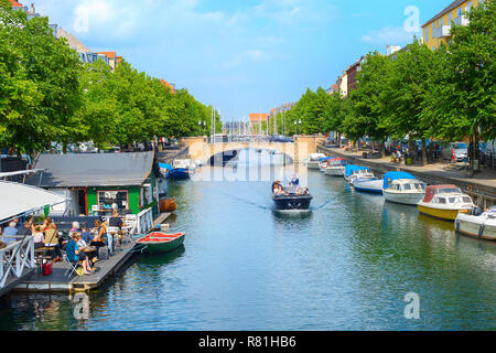 COPENHAGEN, DENMARK - JUNE 14, 2018: People in a riding boat and eating at waterfront restaurant  in Copenahgen. Copenhageni s the capital of Denmark - Stock Image