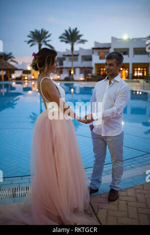 Happy newlyweds stand holding hands next to the swimmimg pool against background of evening lights during the honeymoon in Egypt. - Stock Image