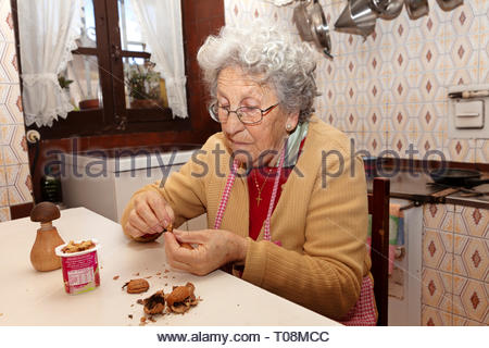 An old woman with sad gesture eats in solitude. - Stock Image