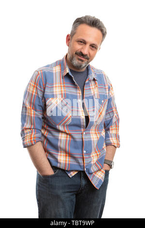Portrait of smiling man wearing plaid shirt holding hands inside jeans pockets as casual male fashion isolated on white studio background - Stock Image