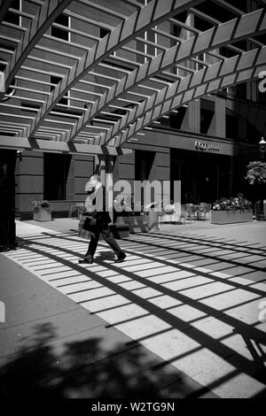 A business man in a suit walks under shadows cast from an overhead latticework roof in EQT Plaza, downtown Pittsburgh, Pennsylvania, USA.  b&w - Stock Image