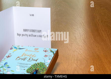Fathers day card on wooden table with a box of chocolates. - Stock Image