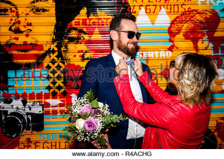 Couple of newlyweds pose in front of a graffitied metal blind - Stock Image