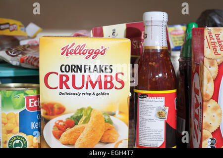 A box of Kellogs Corn Flakes Crumbs in the pantry with other groceries and food stuffs. - Stock Image
