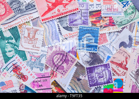 Old Used United States Postage Stamps in a Pile Background. - Stock Image