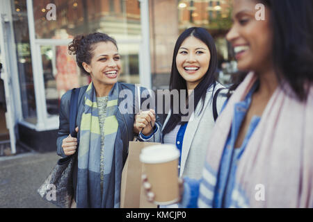 Smiling women friends with shopping bags and coffee outside storefront - Stock Image