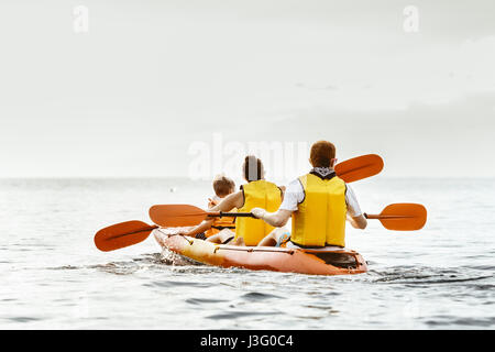 Family of three people swims by kayak at calm sea - Stock Image
