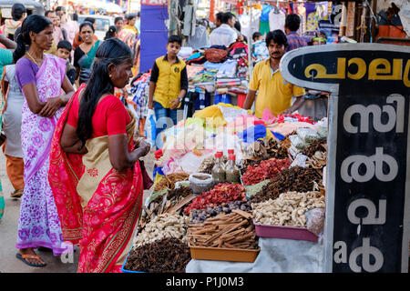A woman wearing a saree buys spices at a street market in Alappuzha (Alleppey), Kerala, India. - Stock Image