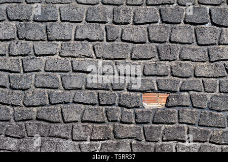 Building wall with uneven brick stones. Repair concept - Stock Image