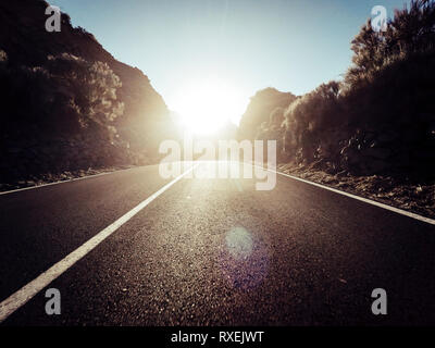 Long way road at the mountain with sun in front and sunlight effect - ground point of view with black asphalt and white lines - driving and travel con - Stock Image