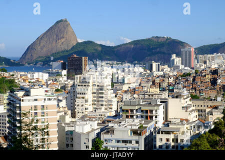 View of a favela with the Sugar Loaf in the background, Rio de Janeiro, Brazil - Stock Image